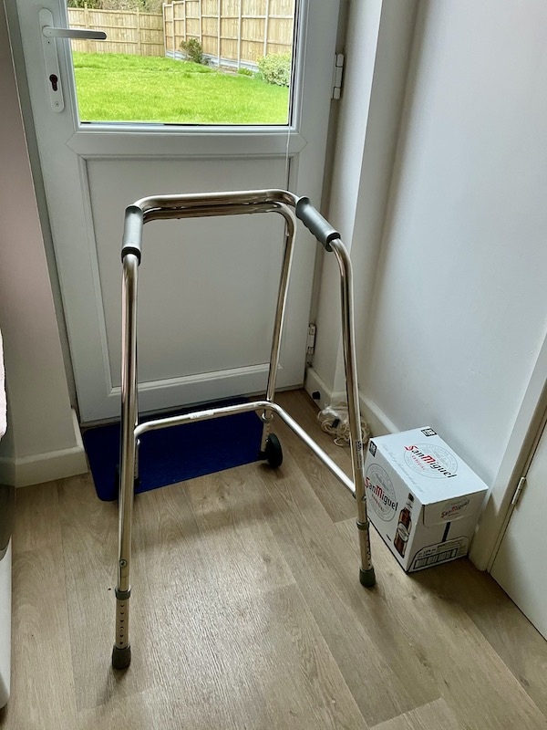 A zimmer frame next to a box of San Miguel beer.