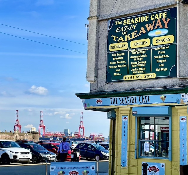 The seaside cafe, with cars parked in the near side, and dock cranes in the distance