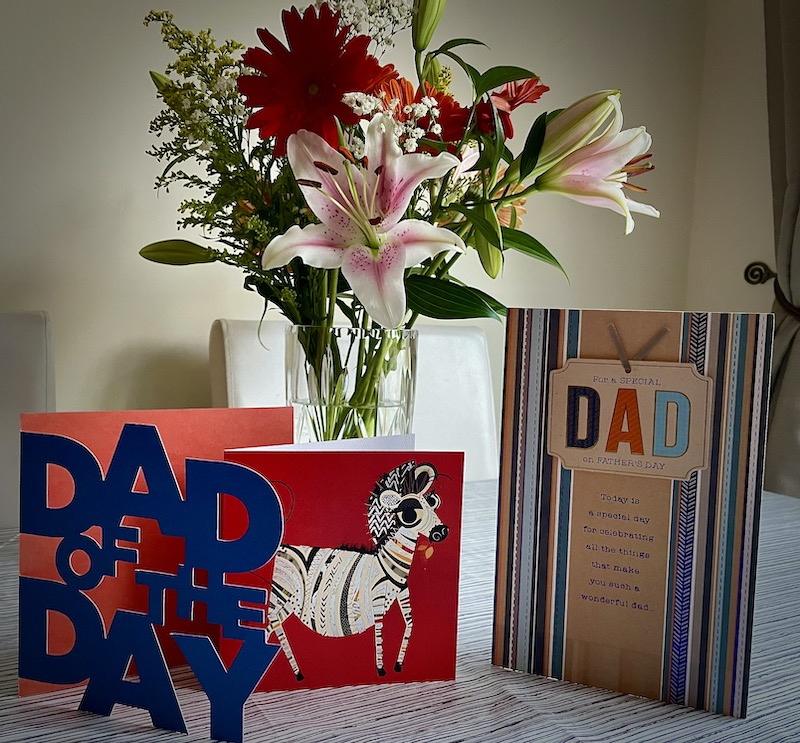 A bunch of flowers in a vase with Father's Day Cards