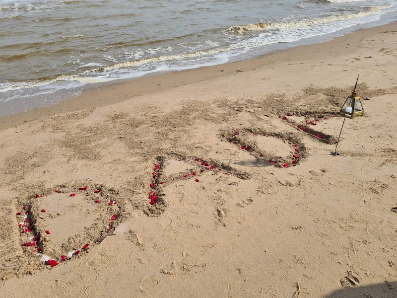 The letters DADA carved into the sand with ashes and petals and a lamp
