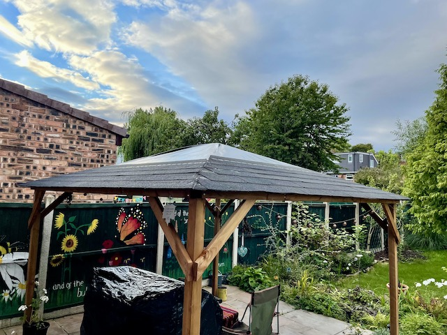 Wooden gazebo with roof tiling half done